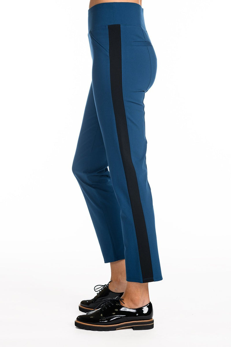One model wearing a ladies technical stretch tuxedo pant in azure with a black side stripe on a white background.