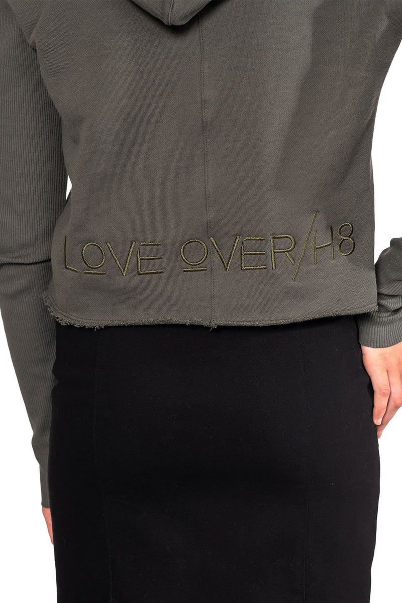 "One model on a white background wearing a ladies designer French terry hoodie in army embroidered with ""Love Over H8"" at the back hem."