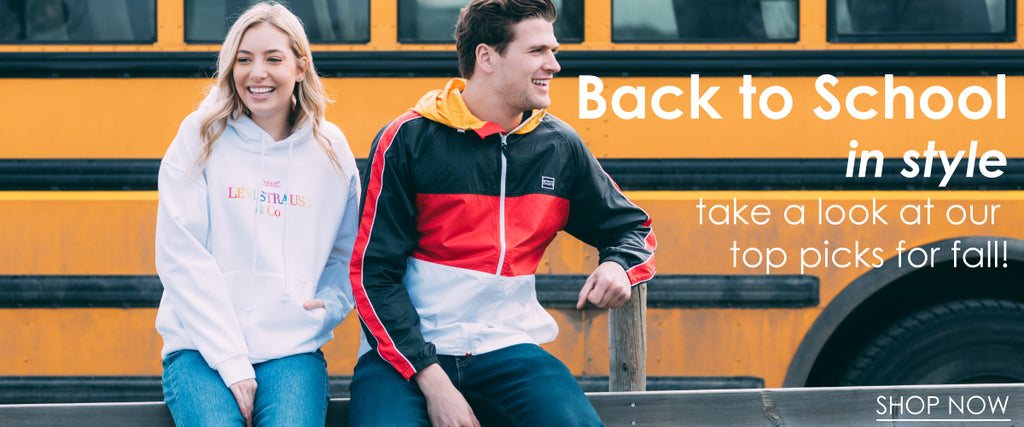 back to school collection; man and woman sitting in front of school bus wearing levi's hoodie and levi's jacket