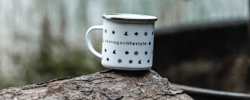 Shop Okanagan Lifestyle online, photo of an email camp mug with okanagan lifestlye logo and small icons sitting on a log at the beach