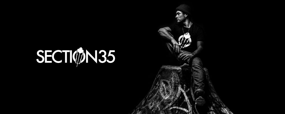 Section35 brand image. Indigenous Man sitting on a tree trunk wearing a Section35 tshirt.