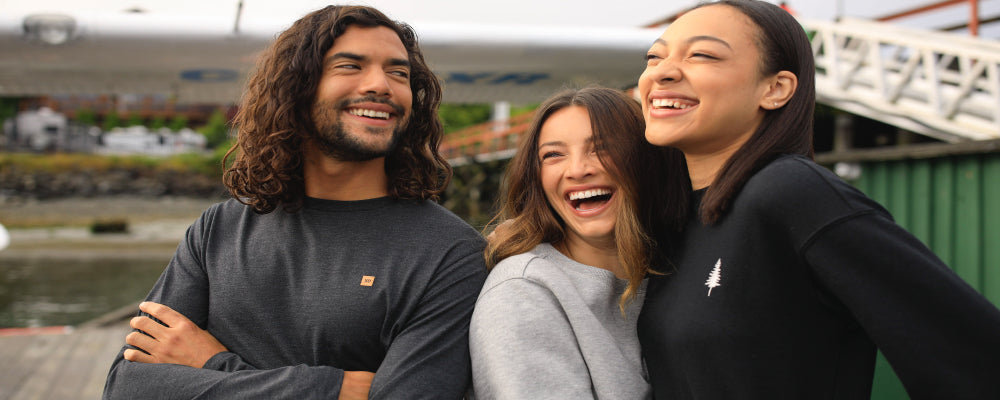 2 women and 1 man laughing together while wearing tentree clothing. 10 trees planted for every purcahse.