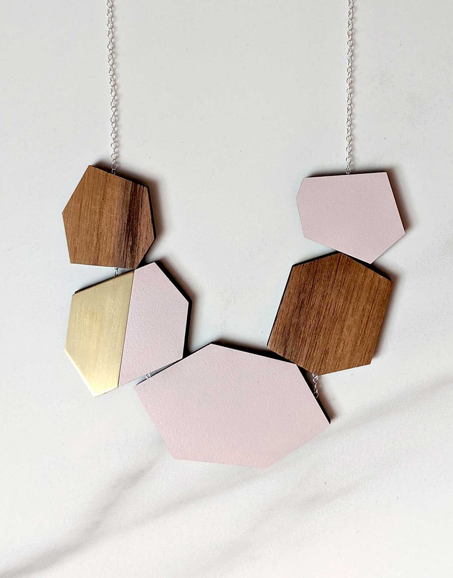 wooden statement necklace in pink and brass close up