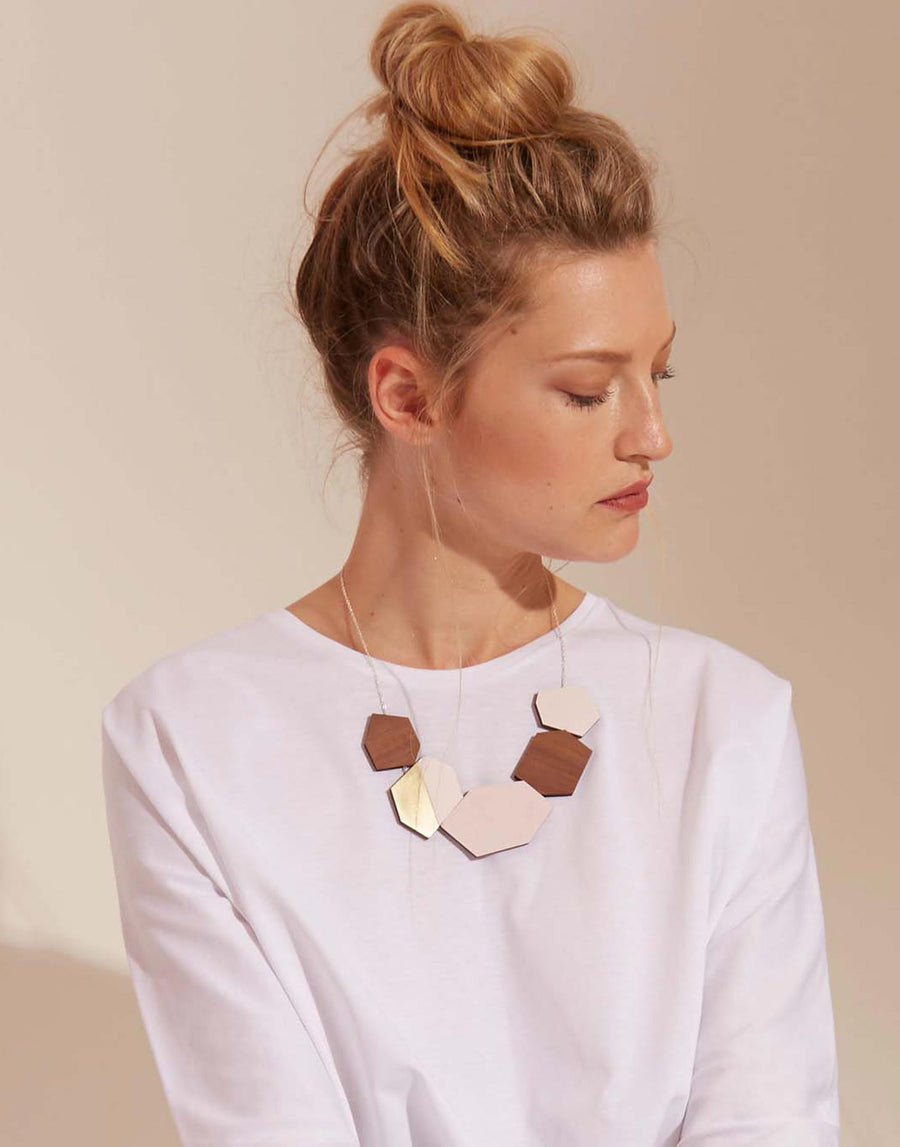 wooden statement necklace in pink and brass on model
