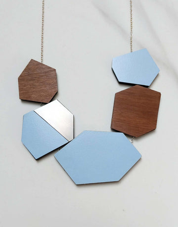 steel statement necklace with blue formica in close up