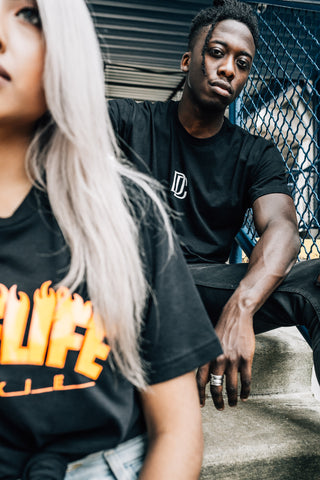 Man and Woman wearing black bike life t-shirts, sitting on stairs.