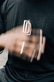 Man waving hand in front of black t-shirt with DC on the chest.