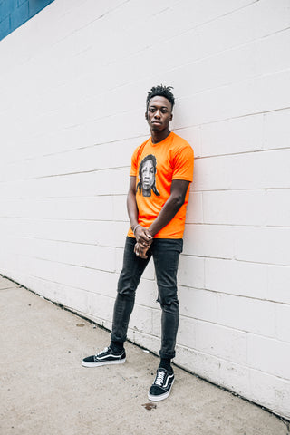 Man standing against a wall wearing an orange docket t-shirt found on MeekMill.com