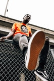 Man sitting on a fence wearing an orange docket t-shirt found on MeekMill.com