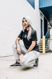 Woman crouching in black DC logo tshirt. Found on MeekMill.com