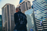 Person in city wearing a black Dream Chasers Motivation windbreaker found on MeekMill.com
