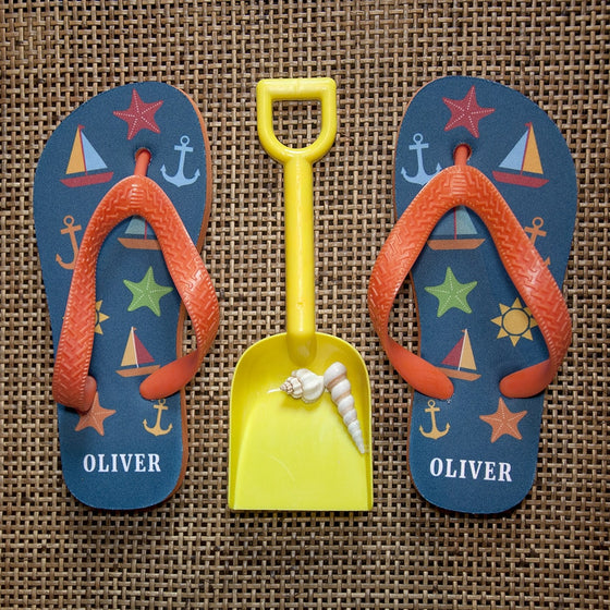 childs boat and anchor style flip flops in navy and orange displayed with spade and shells on a hessian background