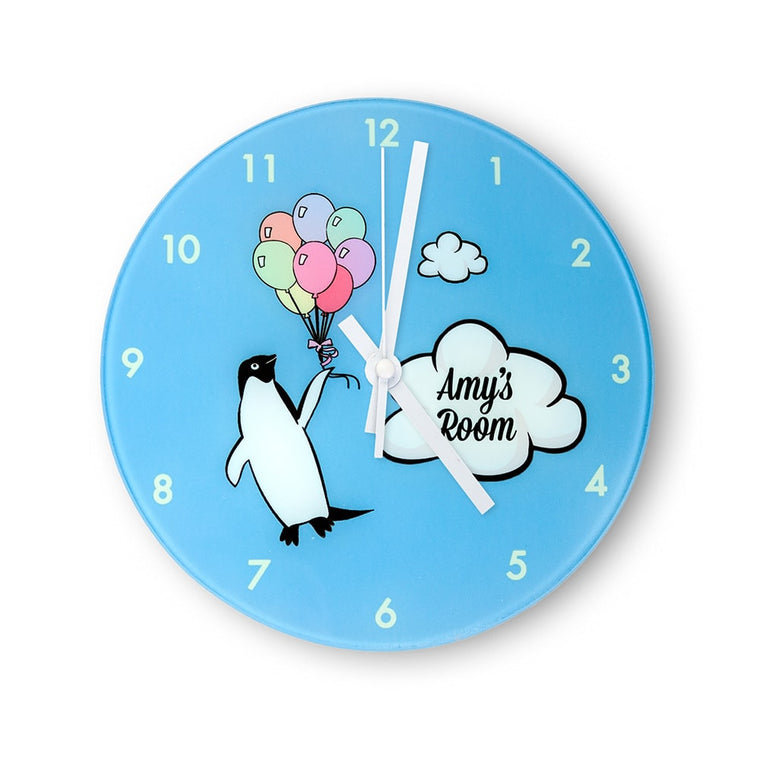 childs wallclock with pale blue background and displaying a penguin holding a bunch of colourful ballons next to a cloud that says the recipients name and the word 'room'.