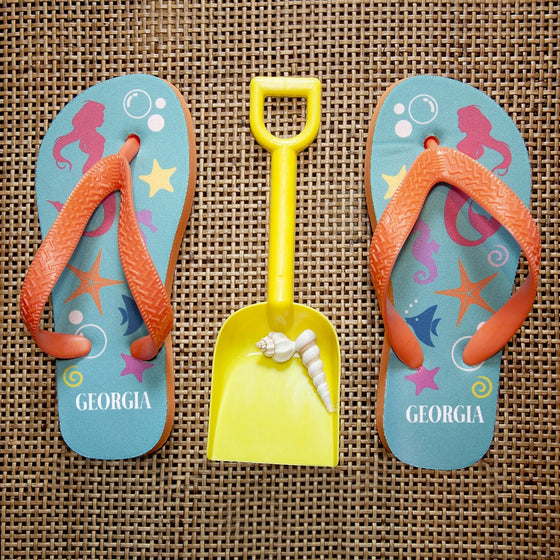 childs mermaid design flip flops in blue and orange displayed on hessian with a spade.