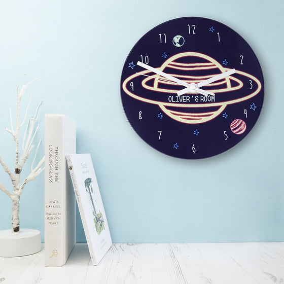 childs wallclock with large hands displaying a planet with rings, on a night sky background. Childs name appears on the planet ring.