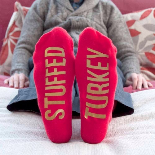 red xmas socks displaying undersoles and message