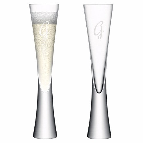 2 champagne flutes one full, one empty, with an initial on each