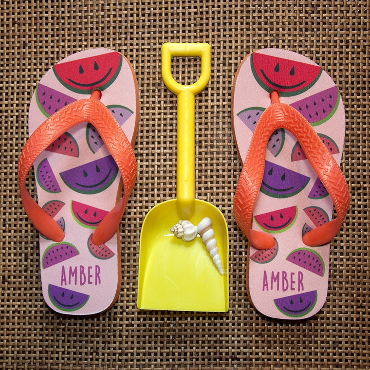childs watermelon design flip flops in pink and orange displayed on hessian with a spade.