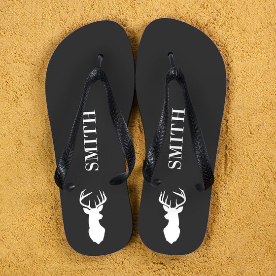 grey base flip flops with black straps and recipients name along the centre in white. Stag head on the heel in white.