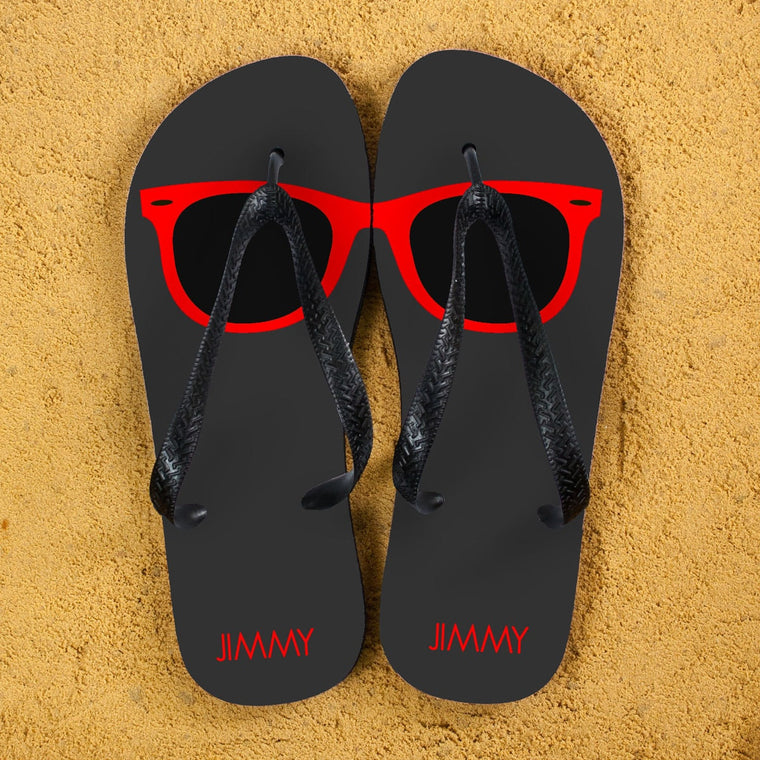 Dark Grey flip flops with black straps and a red sunglasses lens printed across the top of each flipflop.