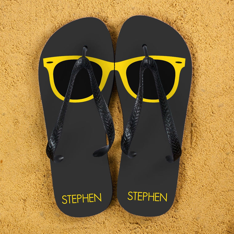 Grey flip flops with black straps and a yellow sunglasses lens printed across the top of each flipflop.