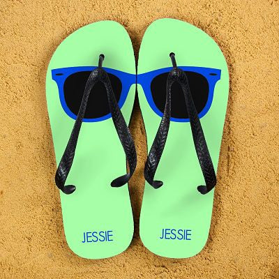 bright green flip flops with a blue single lens sunglass on each shoe. Name of the recipient is displayed on the heel.