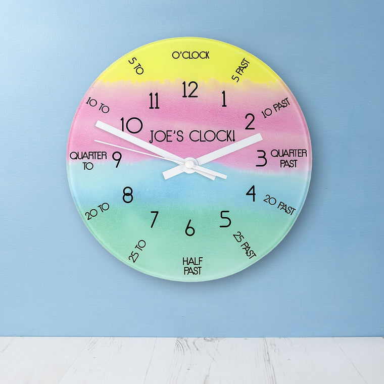 Childs wallclock that shows the time in hours and 5 minutes segments around the clock.In soft yellow,pink,green and blue merging horizontal stripes.
