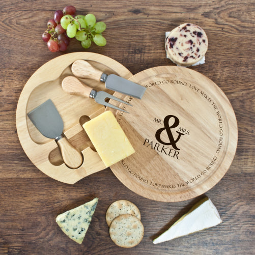 Round wooden cheeseboard showing swing out integrated cheese knife compartment and name of recipients in the centre of the board