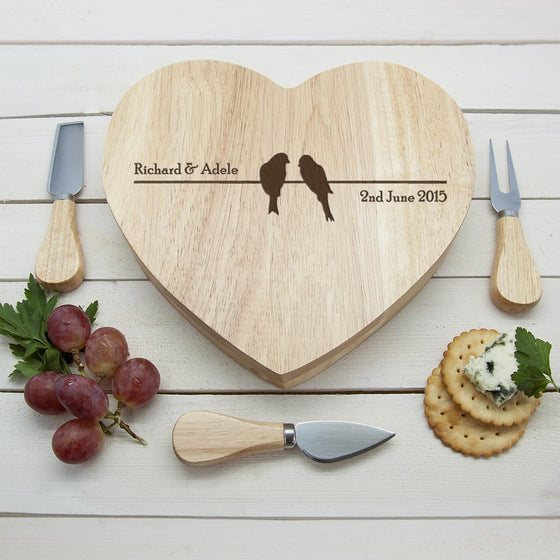 heart shaped wooden cheeseboard with two lovebirds sitting on a wire.