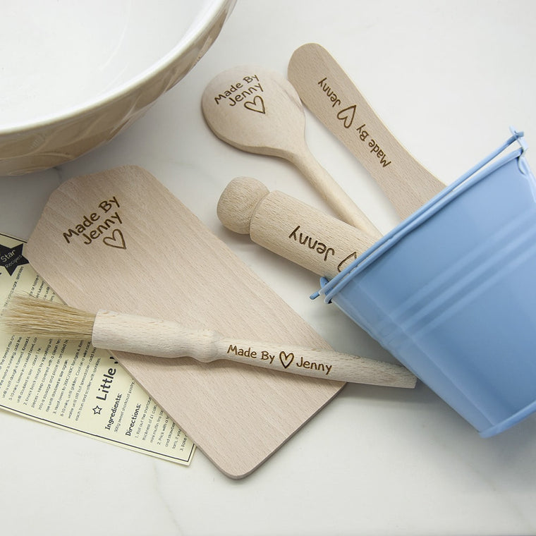 mini sized baking utensils displayed in a light blue bucket. The utensil ends show  'Made by' and the name of the child