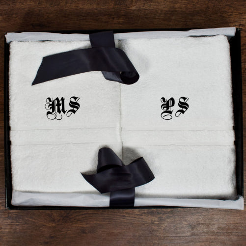 white bath towel with two initials in medieval black font