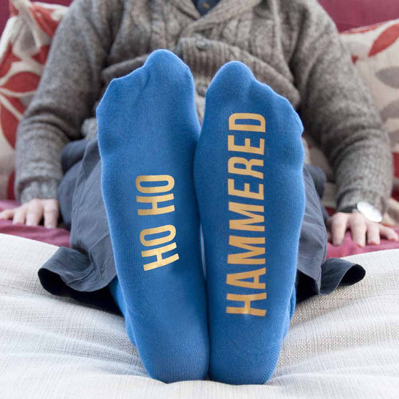 pair of blue printed slogan socks being worn showing undersoles