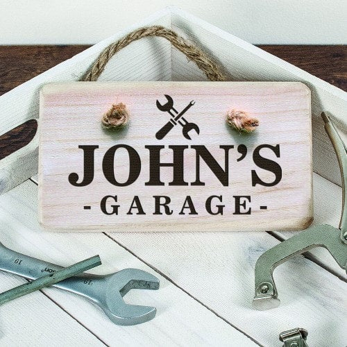 rectangular wooden sign with rope hanger and Johns garage etched