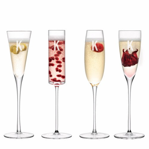 mismatched full champagne flutes with engraved initial