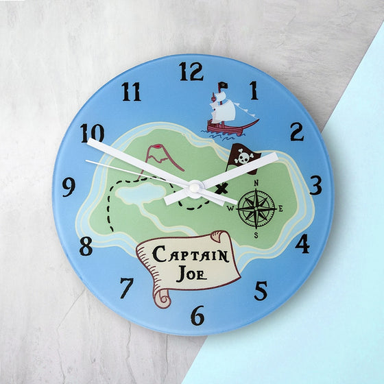 childs wall clock with large hands and blue background. The treasure map in the centre includes a ship, compass and route. Childs name appears between digits 6 and 7.