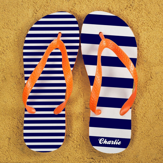 A pair of flip flops in blue and white stripes with orange straps. Narrow stripes on one flip flop and wide stripes on the other. Recipients name on the heel of the right foot.