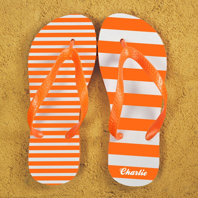 A pair of flip flops in orange and white stripes with orange straps. Narrow stripes on one flip flop and wide stripes on the other. Recipients name on the heel of the right foot.