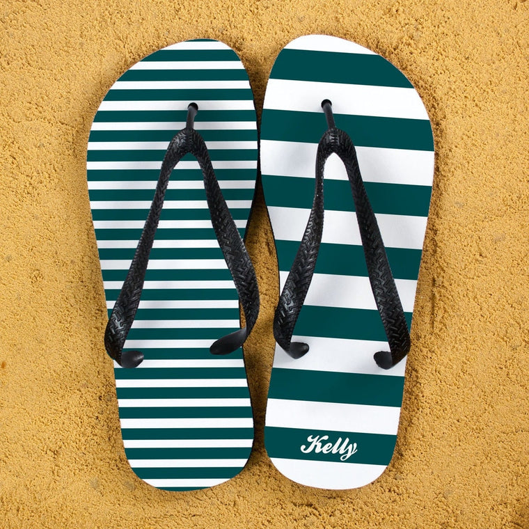 A pair of flip flops in teal and white stripes with teal straps. Narrow stripes on one flip flop and wide stripes on the other. Recipients name on the heel of the right foot.