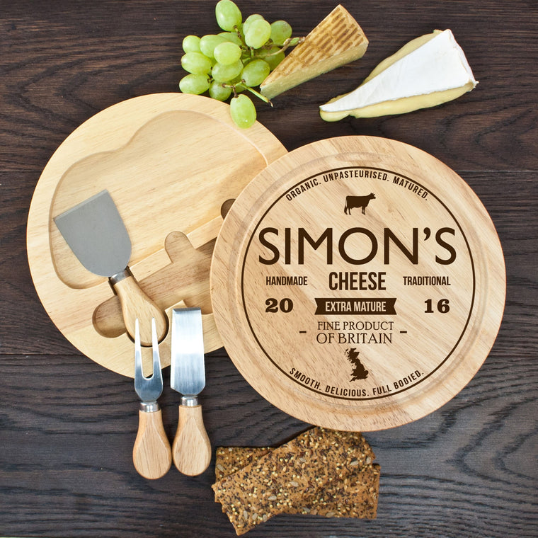 Round wooden cheeseboard showing swing out integrated cheese knife compartment, with cheese knives and name of recipient 'simon's' in the centre of the board.