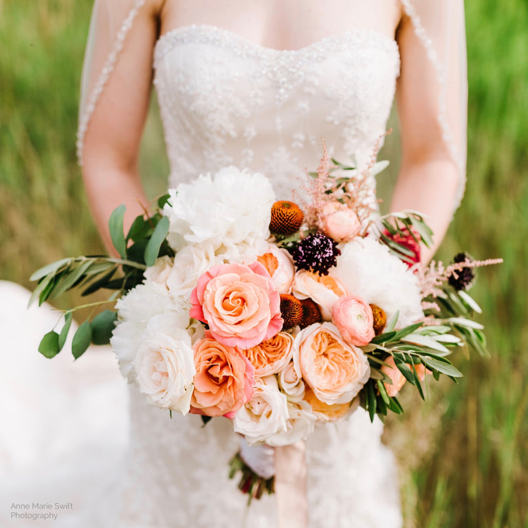 Bride's wedding bouquet with peonies, garden roses, and echinacea pods.