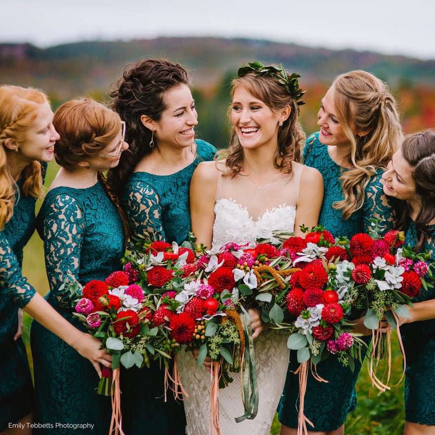 Bride and bridesmaids with fall bouquets in crimson, sage, and copper.