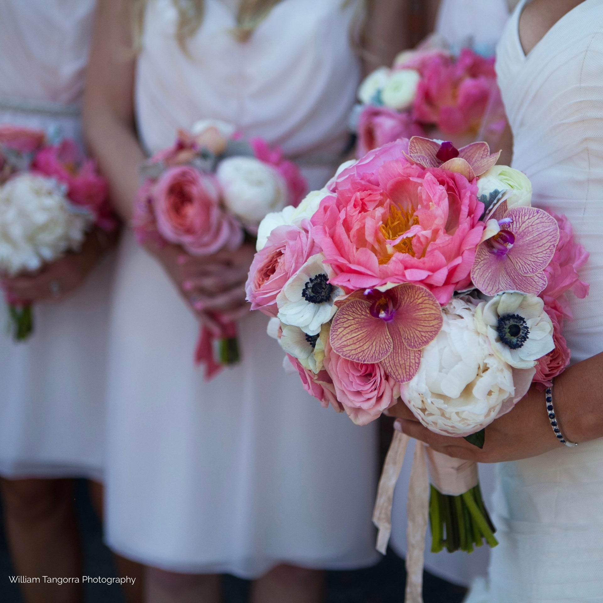 Bridesmaid's bouquet with coral peonies, anemones, and orchids.