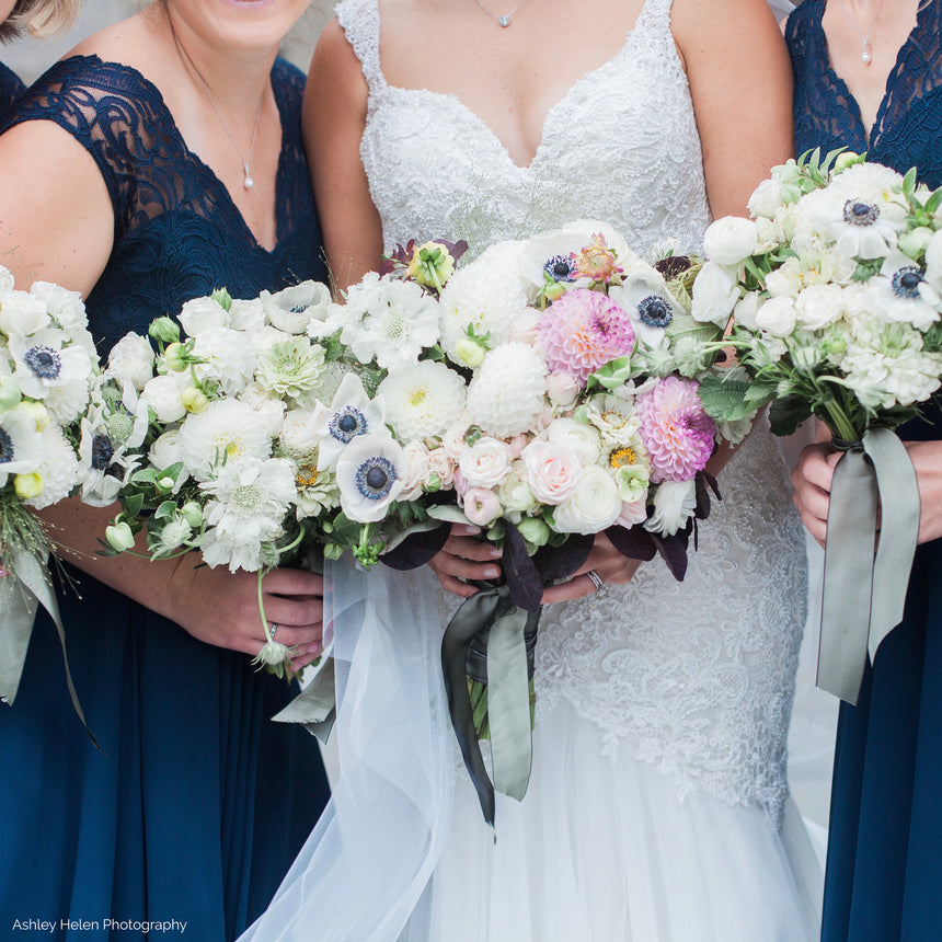 Bridal party bouquets in white, navy, and pink with anemones and dahlias.