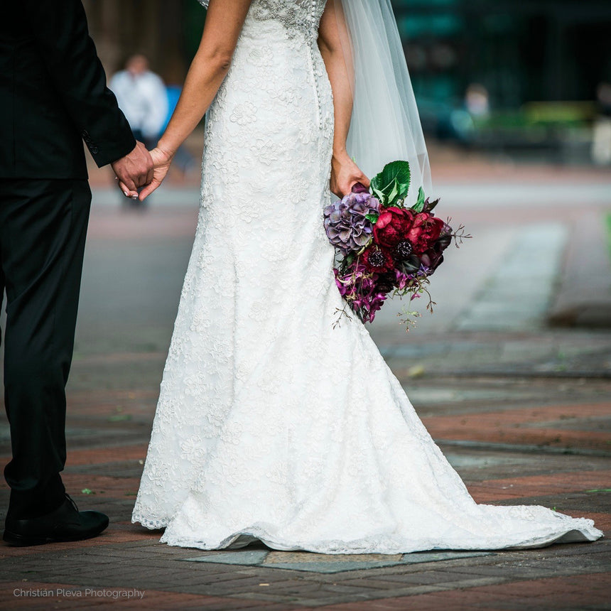 Bride and groom with bouquet in purple and deep red.