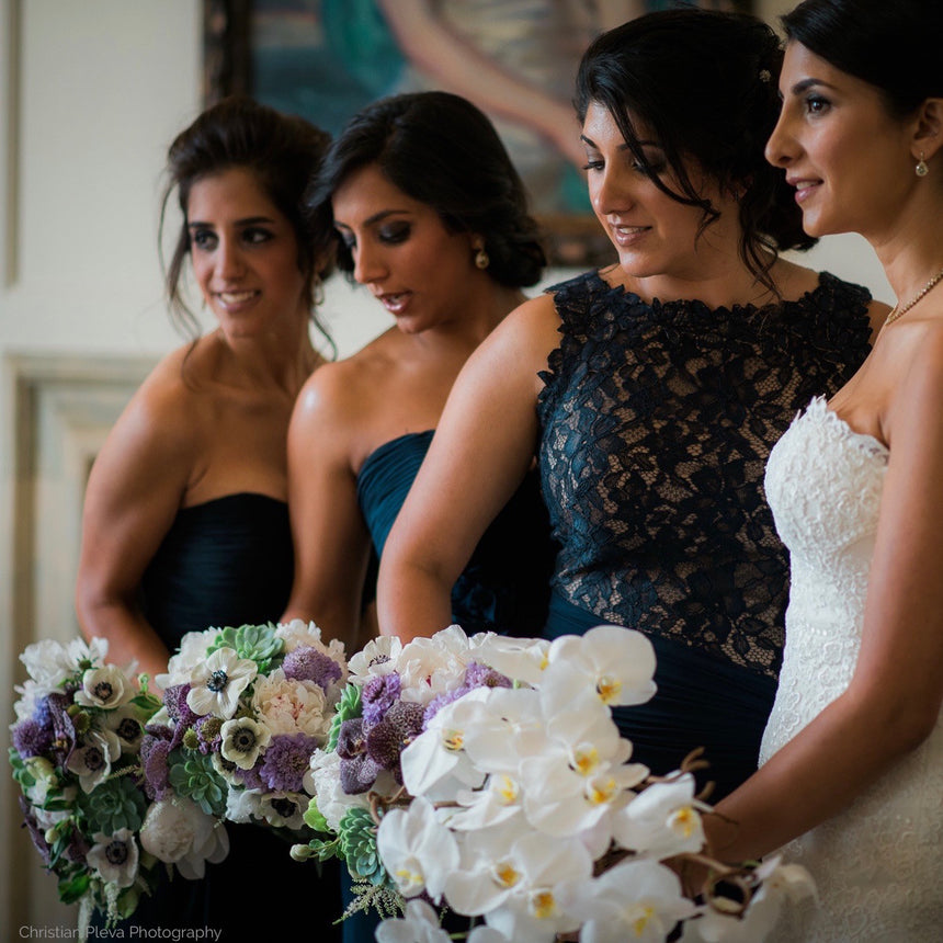 Bride and bridesmaids with spring bouquets in lavender, sage, and white.