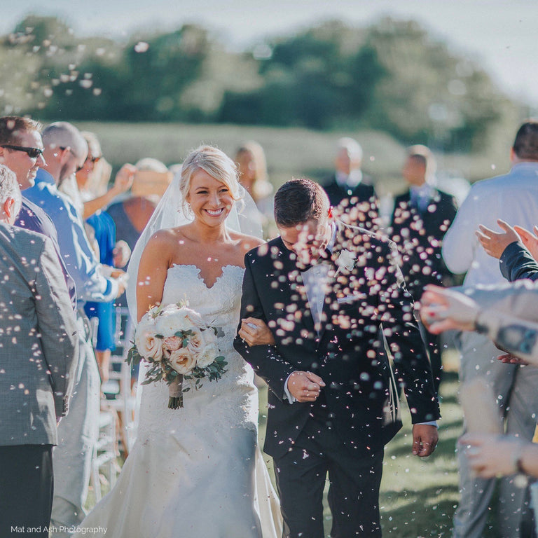 Bride and groom with bouquet and flower petals.