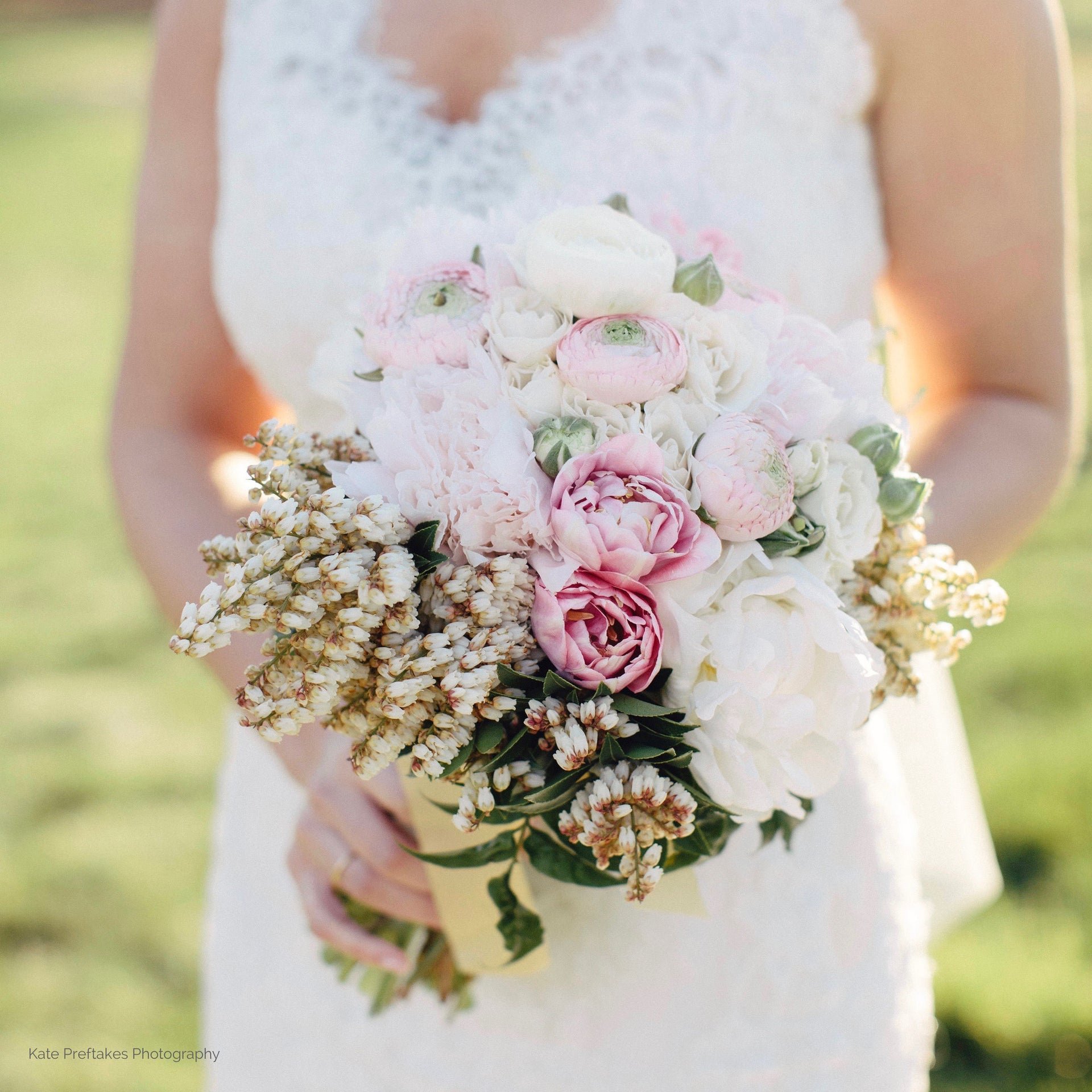 Bride holding flower bouquet in white and pink with tulips and peonies.
