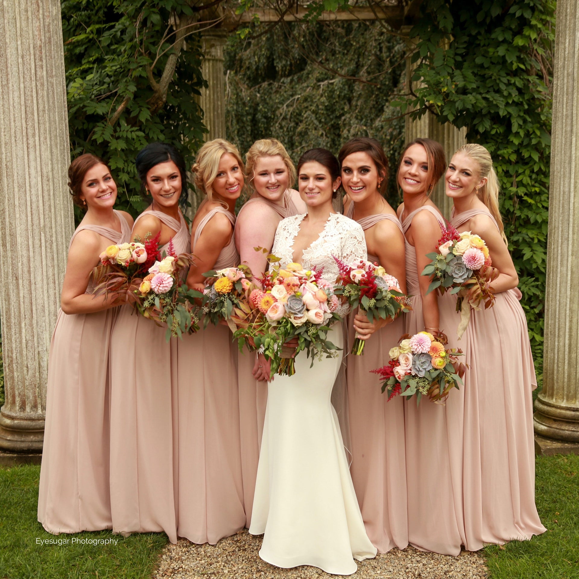 Fall bridal party bouquets in blush, sage, copper, and deep red.