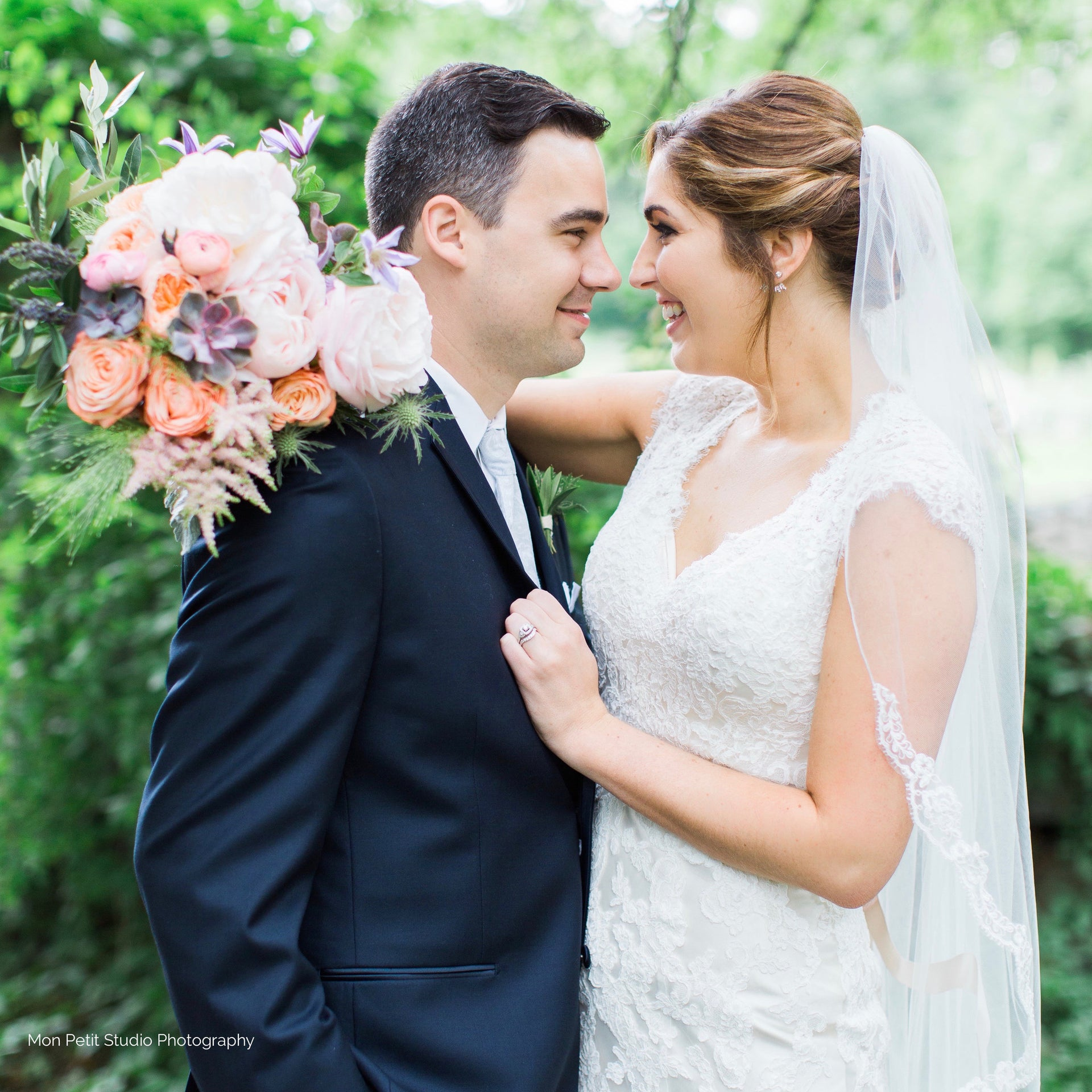 Bride and groom with bridal bouquet in pale pink, blush, and sage green.