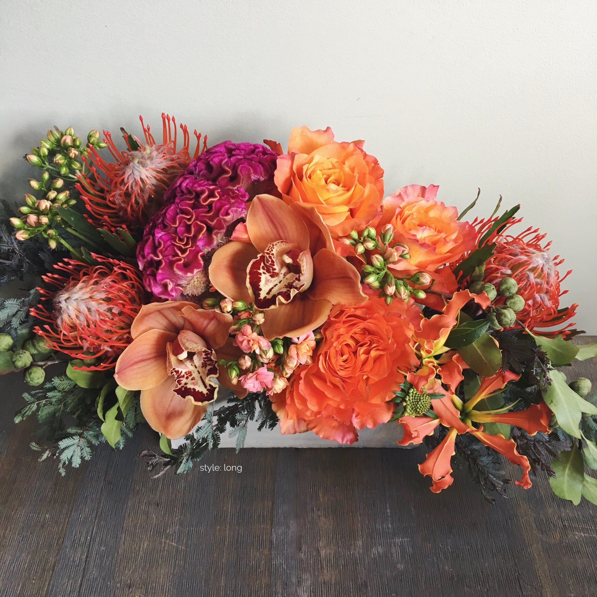 Long and low fall arrangement using orchids, roses, and pin-cushion protea.